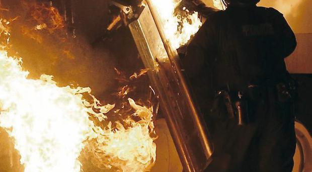 The policeman (centre) is engulfed in flames