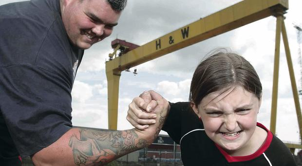 Sean O'Hagan, from Co Down, is put to the test by Jasmine, event organiser Glenn Ross's daughter, ahead of the Belfast Ultimate Strongman Giant Weekend