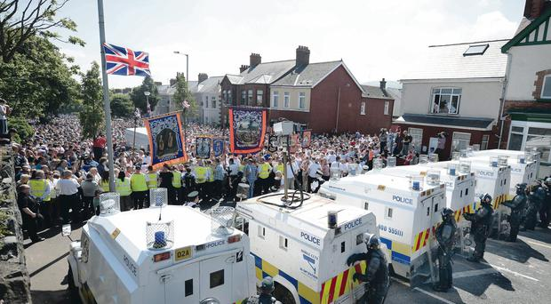 Loyalist protesters march up to police lines on Belfast's Woodvale Road