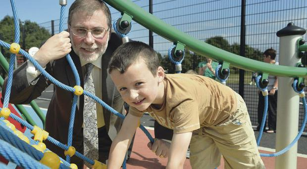 Tiernan Doyle (7) enjoys the Ballysillan Play Park with Social Development Minister Nelson McCausland