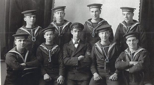 The picture of eight young seadogs and their petty officer found in the pages of a dog-eared Bible