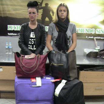 Michaella McCollum Connolly and Melissa Reid stand behind their luggage after being detained at the airport in Lima, Peru (AP)