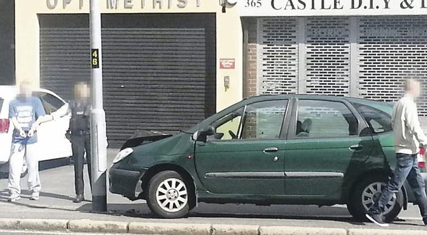 A man is led away by the PSNI after a car crashed on the Antrim Road