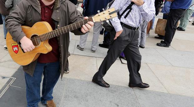 Street busker Fearghus Butler performs in Derry-Londonderry city centre as the all-Ireland Fleadh is getting into full swing with record attendances on the streets, the event runs until Sunday.