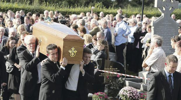The funeral cortege is led through Bellaghy by a piper