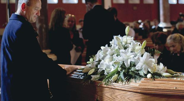A mourner says a final goodbye to Seamus Heaney at his funeral
