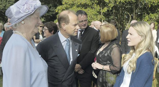 Prince Edward chats to Katie Kirk, who lit the Olympic cauldron to commence the London Olympics, and Dame Mary Peters (left) at a garden party at Hillsborough Castle