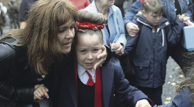 A mother comforts her daughter in the aftermath of a loyalist blast bomb attack outside Holy Cross Primary School in September 2001