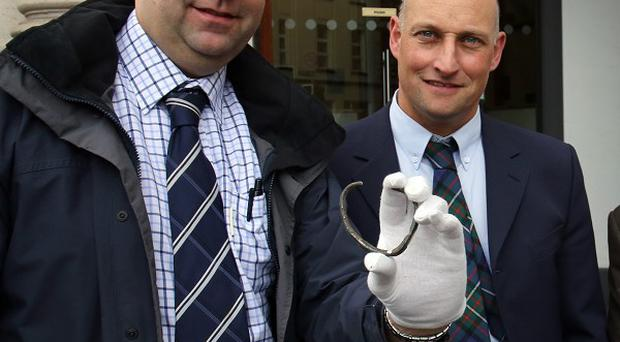 David Taylor, with his brother in-law Andrew Coulter, holds the rare silver Viking ring he discovered on Mr Coulter's farm outside a hearing at Belfast coroner's court