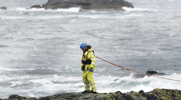 A member of the Coastguard carries out a search on Sunday morning at Ramore Head in Portrush, Co Antrim, for a fisherman who was swept into the sea