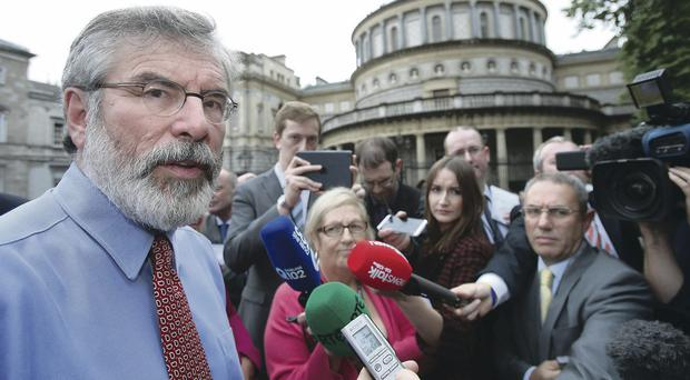 Sinn Fein leader Gerry Adams speaks to the media outside Leinster House in Dublin yesterday