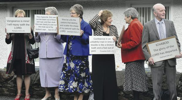 Protesting members of Ballynahinch Congregational Church hold a placard protest outside the church yesterday morning