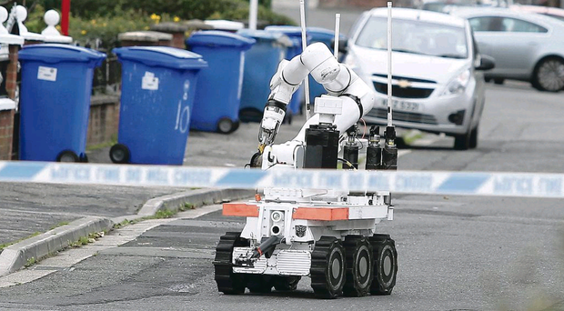 An Army robot examines a suspicious device