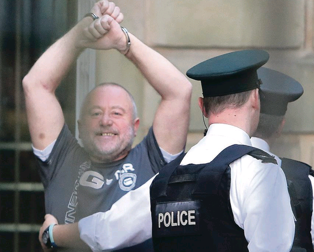 Kieran McLaughlin gestures to family and friends as he enters court on Saturday