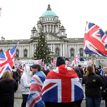 Flag protesters organising a rally in Belfast on one of the busiest shopping days ahead of Christmas were urged to reconsider by Northern Ireland Secretary Theresa Villiers