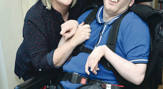 Beryl Patton with her son Ben, who has been waiting for weeks for the health service to get his broken wheelchair fixed