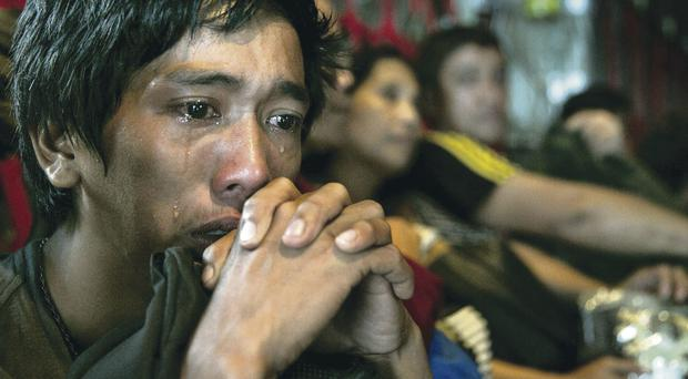 A typhoon survivor is overcome by grief as he is evacuated from the disaster zone