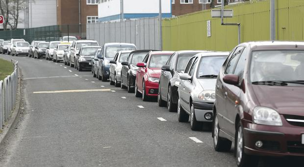 The queue for the car park at the Royal Victoria Hospital and, inset, a van and a skip block a disabled parking space on site