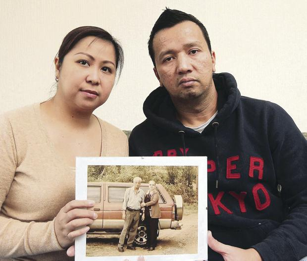 Rick Lapuz and wife May with a picture of his father Rudy, who died during Typhoon Haiyan