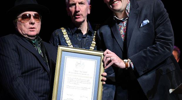 Lord Mayor Mairtin O Muilleoir (centre) and Alderman Gavin Robinson present a framed commemorative scroll to Van Morrison