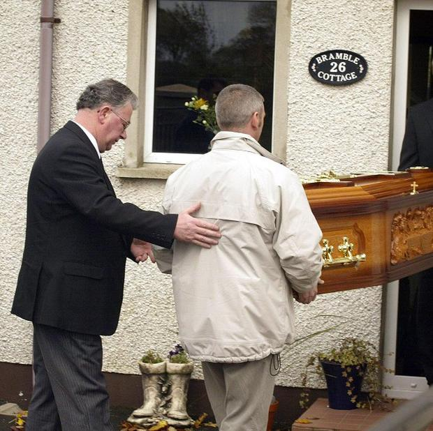 Family members carry the remains of Jean McConville into her son Michael McConville house, at Crumlin Co Antrim