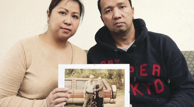 Rick Lapuz, originally from the Philippines, holds a picture of his father Rudy who died during Typhoon Haiyan which devastated the Philippines earlier this week. Mr Lapuz is pictured at his home in east Belfast with his wife May.