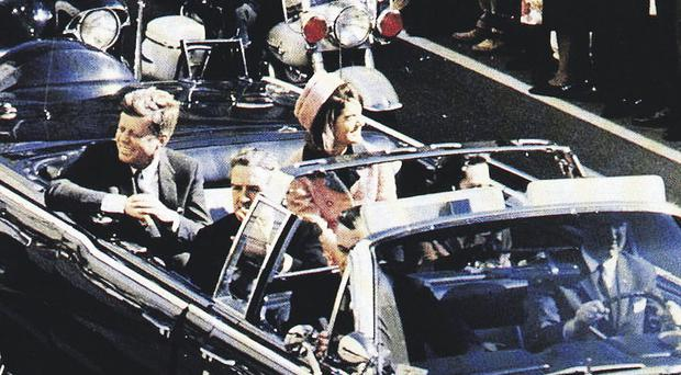 US President John F Kennedy sitting in the back of the car in Dallas driven by William Greer just moments before his assassination