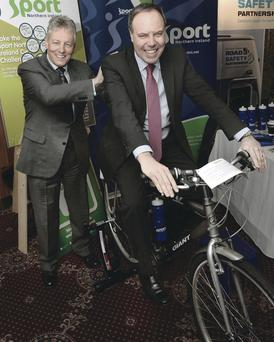 First Minister and DUP leader Peter Robinson gives deputy Nigel Dodds a push on a NI Sport timed cycle challenge at the annual party conference in La Mon House