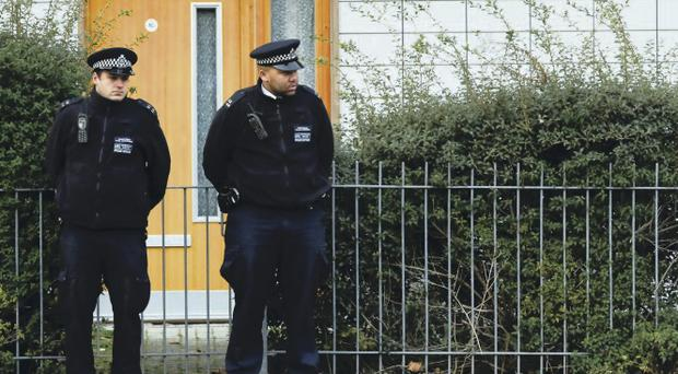 Police stand guard outside a south London block of flats being investigated in connection with alleged slavery