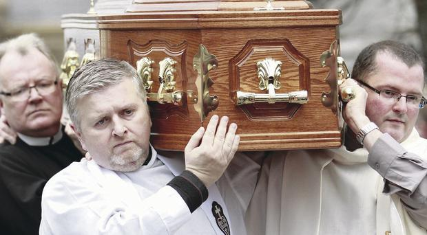 Priests carry Father Alec Reid's coffin at the funeral
