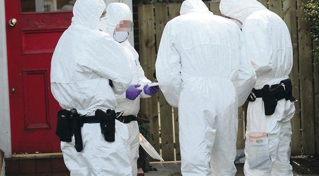 Forensic officers at the scene after a bomb was placed under a police officer's car in east Belfast last December