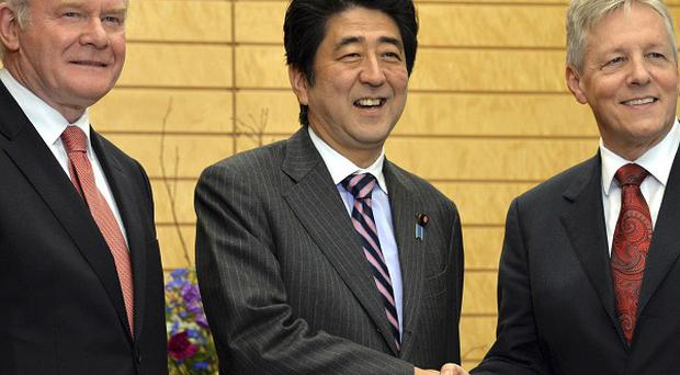 Japanese prime minister Shinzo Abe shakes hands with First Minister Peter Robinson while Deputy First Minister Martin McGuinness looks on
