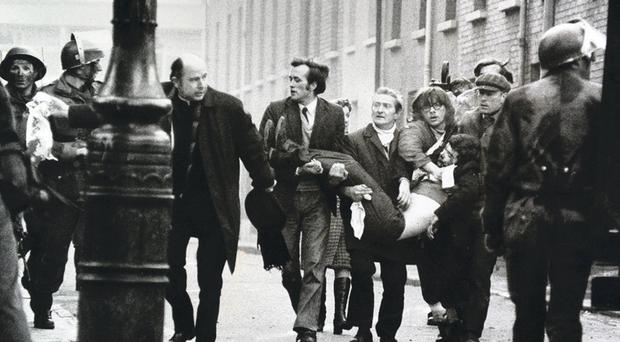 The then Fr Edward Daly, waving his bloodstained handkerchief, as one of the thirteen dead victims is carried behind, is an iconic image from Bloody Sunday