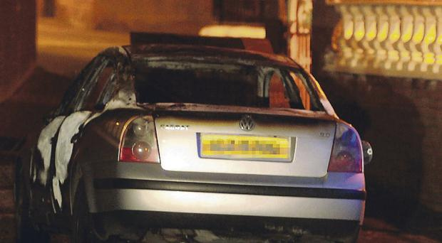 The burnt-out suspected getaway car used by dissidents in gun attack on police