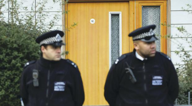Police guard the flat where they lived in Brixton