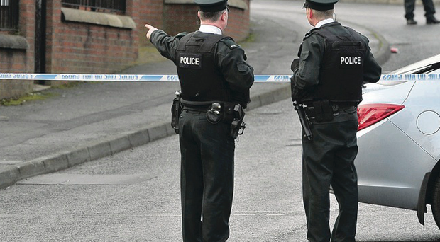Police officers seal off an area in Ardoyne