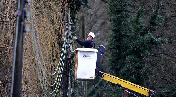 A workman works on repairing electricity lines near Reigate in Surrey after floods hit the area