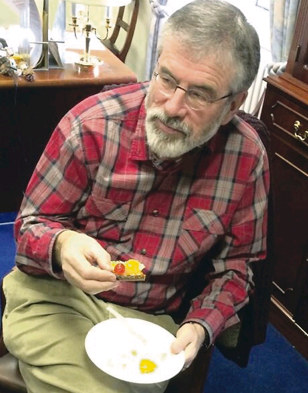 Gerry Adams eats the cake he baked for Peter Robinson's 65th birthday