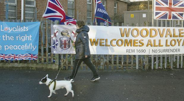 A woman passes the loyalist camp at Twaddell Avenue, Belfast, where an officer was knifed yesterday