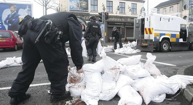 PSNI officers lay down sandbags in the Sailortown area of Belfast
