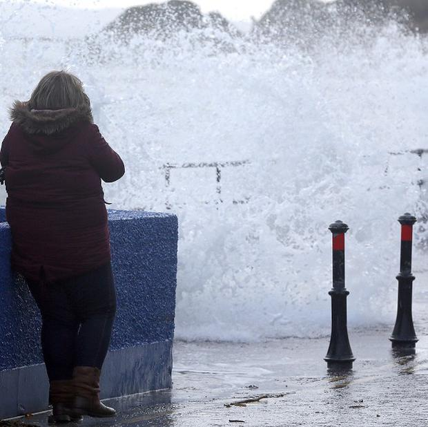 A woman avoids waves, at the walkway at Whitehead in Co Antrim