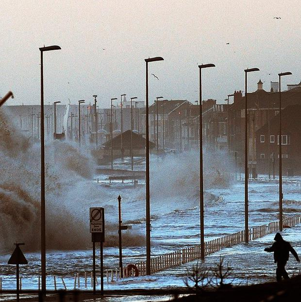 Water covers the coastal roads at Clevelys near Blackpool as large waves crash over the sea defences as high tides and huge waves hit the west coast of the UK.
