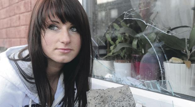 Anna Bloch holds the large brick that was thrown through the window of her house in east Belfast