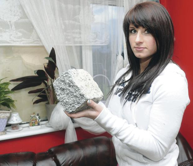 Anna Bloch holds the brick thrown through the window of her home at Inverary Drive in east Belfast