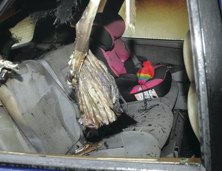 A child's hat yesterday sits on a car seat in the back of a vehicle which was damaged in an arson attack in north Belfast