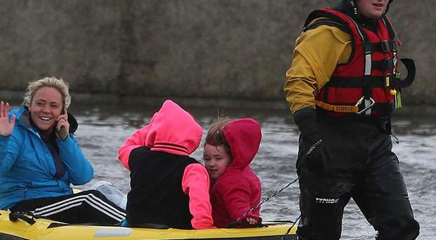 Residents use a boat to navigate flood waters on the Lee Estate in Limerick