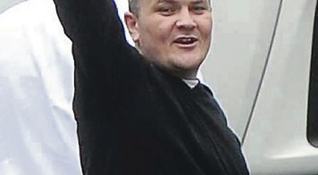 Sean Ruddy waves to family members outside Lisburn Court