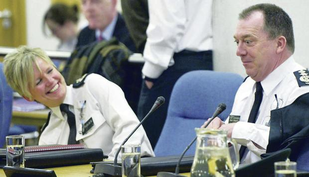 Outgoing PSNI Chief Constable Matt Baggott and outgoing Assistant Chief Constable Judith Gillespie share a joke at Thursday's Policing Board meeting