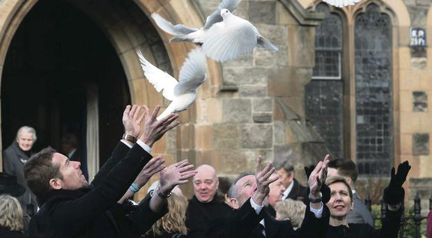 Elizabeth Webster and her children Jamie, Mark and Christopher release doves in memory of her mother-in-law Leila Webster at her thanksgiving service at Saint Mary Magdalene Church of Ireland in Belfast