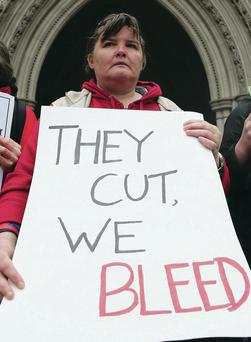 A protester outside London's High Court showing her opposition to proposed changes to the welfare system